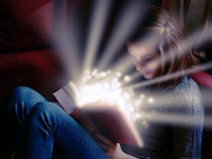 mujer joven con libro que brilla